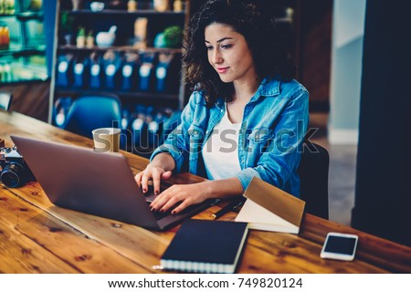 Young beautiful woman dressed in stylish outfit transferring money using online banking service on laptop computer connected to wifi.Skilled female freelancer sending files to customer via gadget