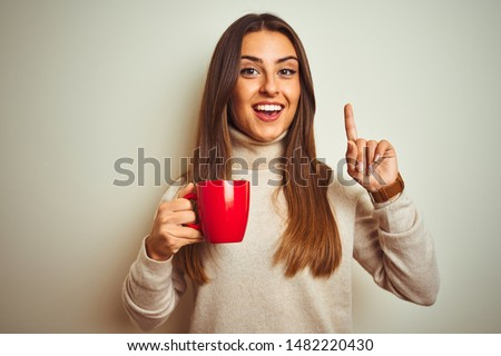 Young beautiful woman drinking red cup of coffee standing over isolated white background surprised with an idea or question pointing finger with happy face, number one