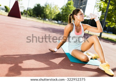 Young beautiful woman drinking water after exercise in a city training court on a sunny day