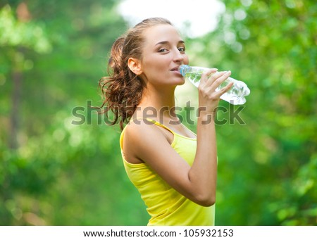 Young beautiful woman drinking water after fitness exercise outdoors