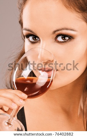 Young beautiful woman drinks wine from wine glass, close up.
