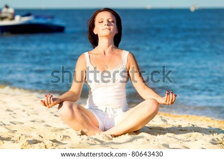 Young beautiful woman during yoga on sea beach