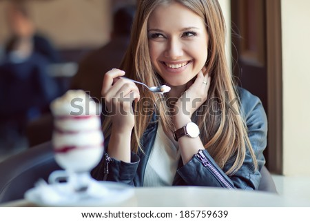 young beautiful woman eating a dessert