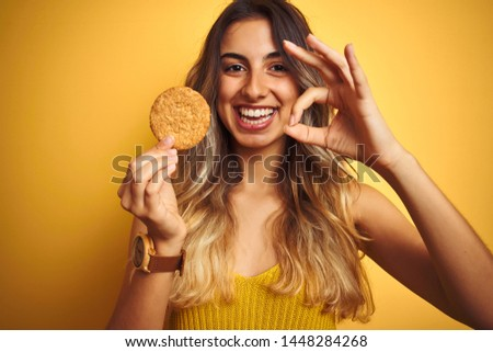Young beautiful woman eating biscuit over grey isolated background doing ok sign with fingers, excellent symbol