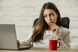 Young beautiful woman enjoying a piece of chocolate at the office table during a coffee break
