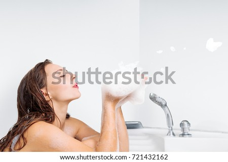Young beautiful woman enjoying bathing in bathtub