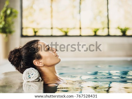 Young beautiful woman enjoying summer holiday in swimming pool at resort hotel. Spa, retreat, relaxation concept. Beauty and body care