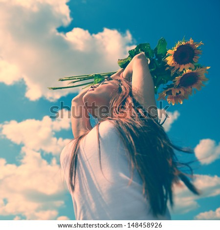 young beautiful woman enjoying summer, youth and freedom, holding sunflowers above head, against blue sky, toned image