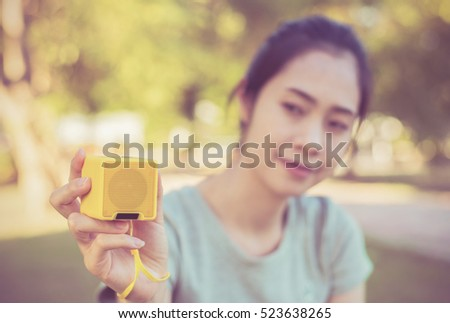 Young beautiful woman enjoying the music at  outdoor park.Woman listening music by Bluetooth speaker at  outdoor park.