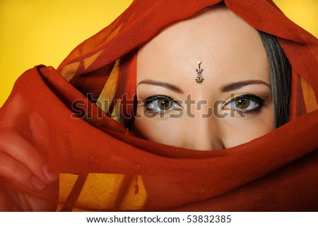 Young beautiful woman eyes in indian traditional jewelery, bindi , sari dress and makeup. yellow background