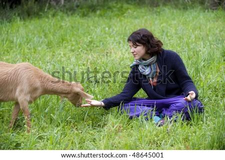Young beautiful woman feeding a goat
