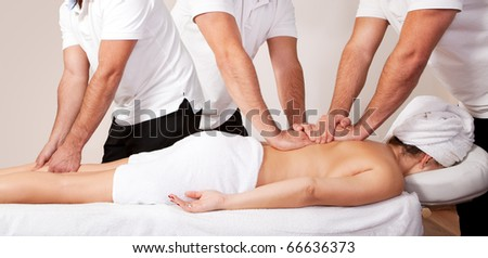 Young beautiful woman getting massage. Three therapists working at the same time