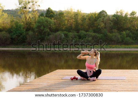 Young beautiful woman girl are doing sport fitness yoga position drink water on a bridge at  lake, sea, see in the water - in the background you can see a colorful sundown - water, orange sundown