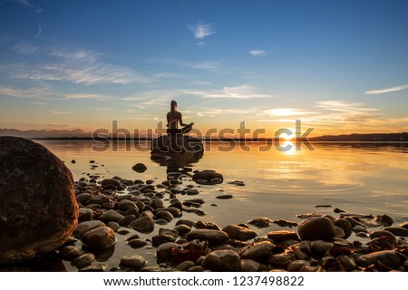 young beautiful woman girl are doing sport fitness yoga position on a stone at a beautiful lake, sea, see in the water - in the background you can see a colorful sundown - stone, water, orange sundown