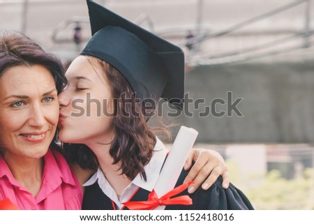 f5991be24ca Young beautiful woman graduate kissing and hugging her mother at graduation  ceremony. Happy loving family
