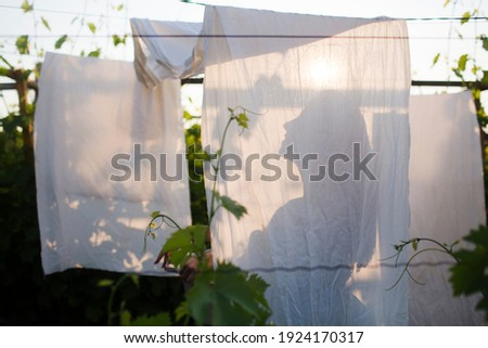 Young beautiful woman hanging up laundry outdoors.  Spring Awakening. cottagecore. slow life. pastoral life.  enjoy the little things.  Dreaming of Spring  Stock photo ©