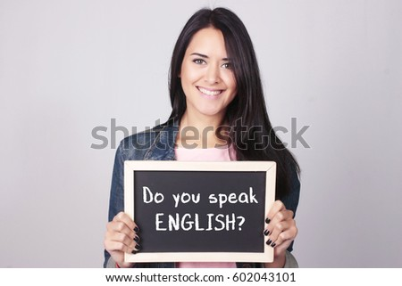 Young beautiful woman holding a chalkboard that says Do You Speak English?