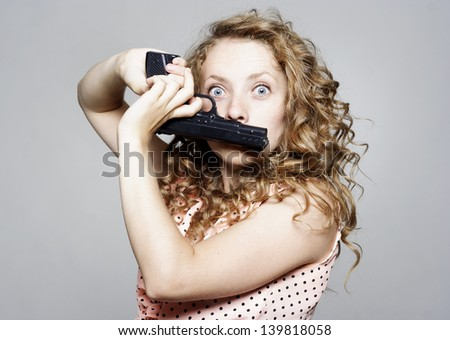 Young beautiful woman holding a gun over her mouth