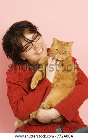 young beautiful woman holding a red domestic cat