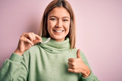 Young beautiful woman holding aligner standing over isolated pink background happy with big smile doing ok sign, thumb up with fingers, excellent sign