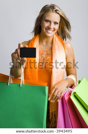Young, beautiful woman holding bags and credit card. Smiling and looking at camera. Showing credit card. Gray background