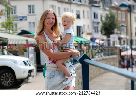 Young beautiful woman holding her little daughter, adorable blonde toddler girl in casual outfit, outdoors in urban environment - mother and child concept
