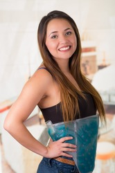 Young beautiful woman holding ice gel pack on her belly, medical concept, in office background