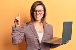 Young beautiful woman holding laptop smiling with an idea or question pointing finger with happy face, number one