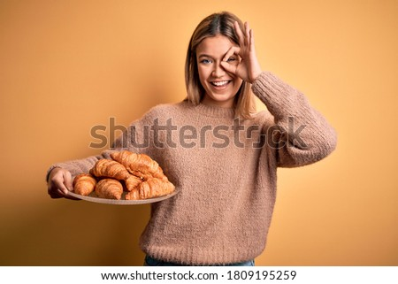 Young beautiful woman holding plate with croissants over isolated yellow background with happy face smiling doing ok sign with hand on eye looking through fingers Stock fotó ©