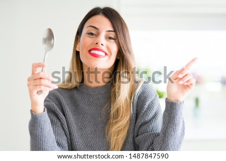 Young beautiful woman holding silver spoon at home very happy pointing with hand and finger to the side