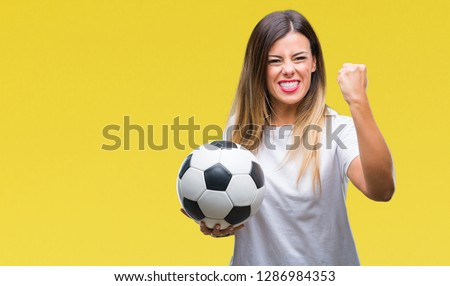 Young beautiful woman holding soccer ball over isolated background annoyed and frustrated shouting with anger, crazy and yelling with raised hand, anger concept