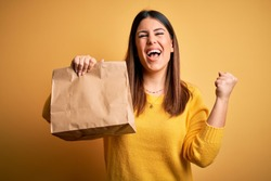 Young beautiful woman holding take away paper bag from delivery over yellow background screaming proud and celebrating victory and success very excited, cheering emotion