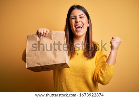 Young beautiful woman holding take away paper bag from delivery over yellow background screaming proud and celebrating victory and success very excited, cheering emotion Foto d'archivio ©