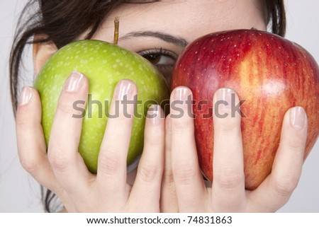 young beautiful woman holding two apples - green and red.