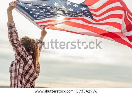 Shutterstock young beautiful woman holding USA flag.