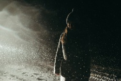 Young beautiful woman in a gray coat and hat stands in the snow at night on a dark background during a snowfall. Winter's tale, sad, cold, blizzard, snow. Emotional girl. Christmas mood, holiday