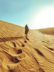 Young beautiful woman in a long dress walks along the sand dunes of the Dubai desert