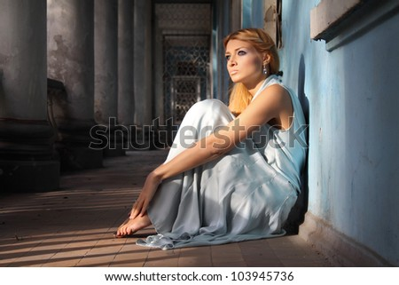Young beautiful woman in a luxurious blue dress on the old villa