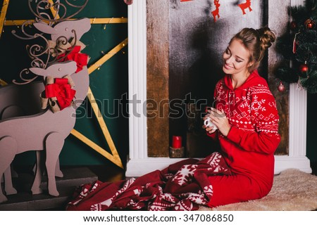 Young beautiful woman in a red warm pajamas with scandinavian ornaments sitting near decorative fireplace and drinking hot tea or cocoa. Christmas mood