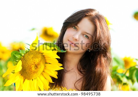 Young beautiful woman in a sunflower field. Summer picnic