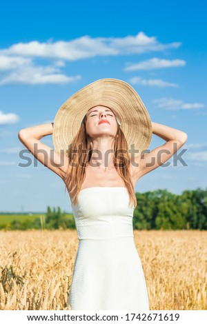 Young beautiful woman in a white dress and a hat on a milf's field. The concept of outdoor recreation, a trip to the village.