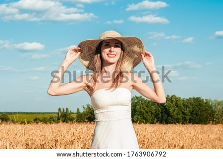 Young beautiful woman in a white dress and a hat on a milf's field. The concept of outdoor recreation, a trip to the village