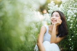Young beautiful woman in a white dress posing in garden
