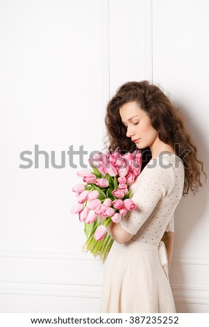 Young beautiful woman in a white knitting dress posing with a bouquet of pink tulips #387235252
