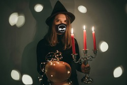 Young beautiful woman in a witch costume with candles, hat, magic, pumpkin in a medical black mask with a skull. Halloween 2020, quarantine, pandemic, spiritually, celebration. Traditional, party