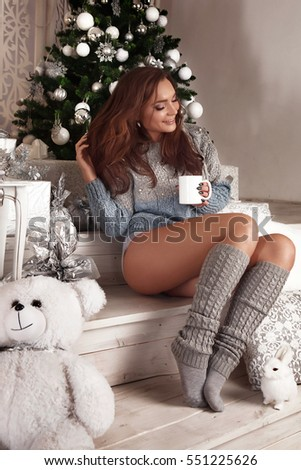 young beautiful woman in blue dress relaxing in christmas decorated interior pretty happy smiling girl