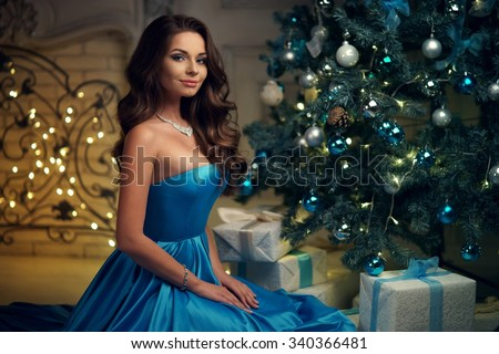Young beautiful woman in blue elegant evening dress sitting on floor near christmas tree and presents on a new year eve. Interior with christmas decorations. Shallow DOF and bokeh background