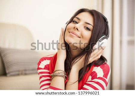 Young beautiful woman in bright outfit enjoying the music at home #137996021