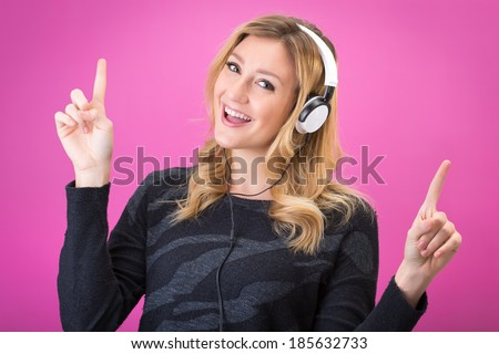 Young beautiful woman in bright outfit enjoying the music with her headphones. Studio portrait on pink background
