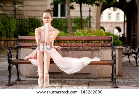 Young beautiful woman in elegant pink dress and ballet shoes on bench in the garden.